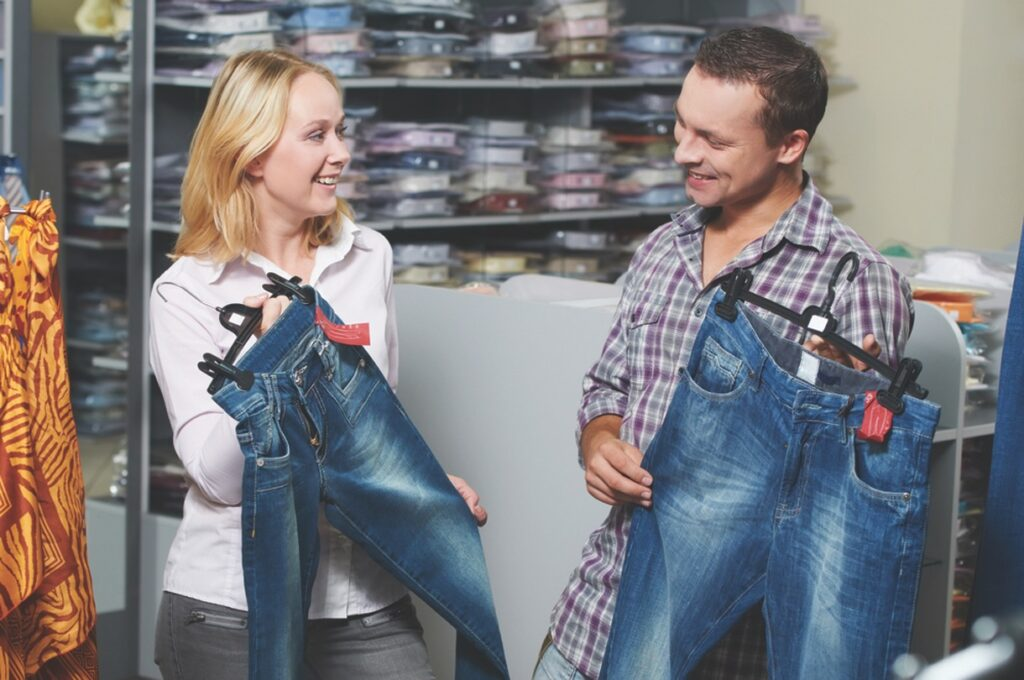 A young woman and a young man hold up jeans to show each other in a store.