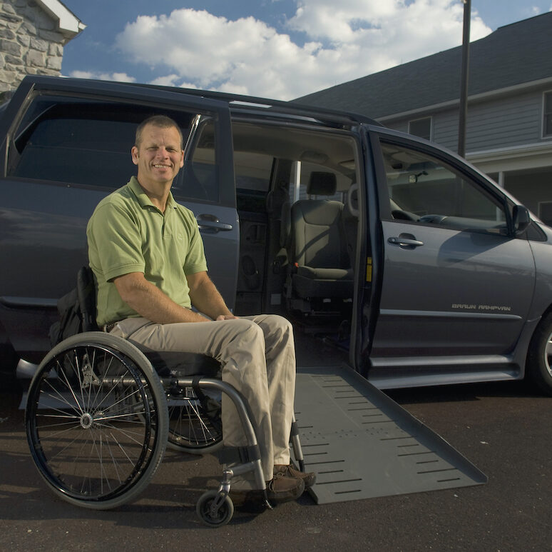 A man sits in a manual wheelchair next to a modified van with the wheelchair ramp outstretched.