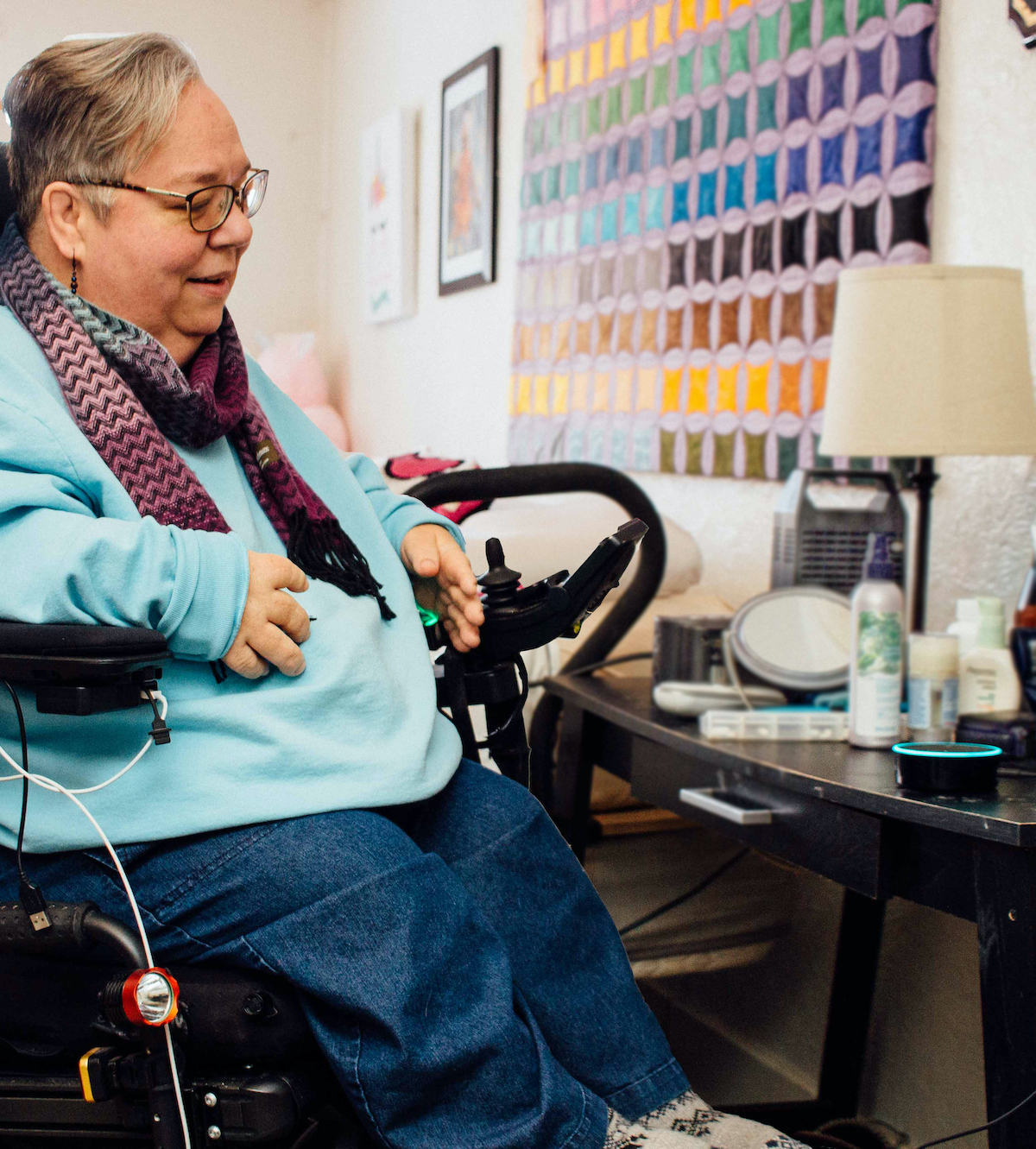 A woman in a power wheelchair speaks to an Amazon Echo Dot on a bedside table.