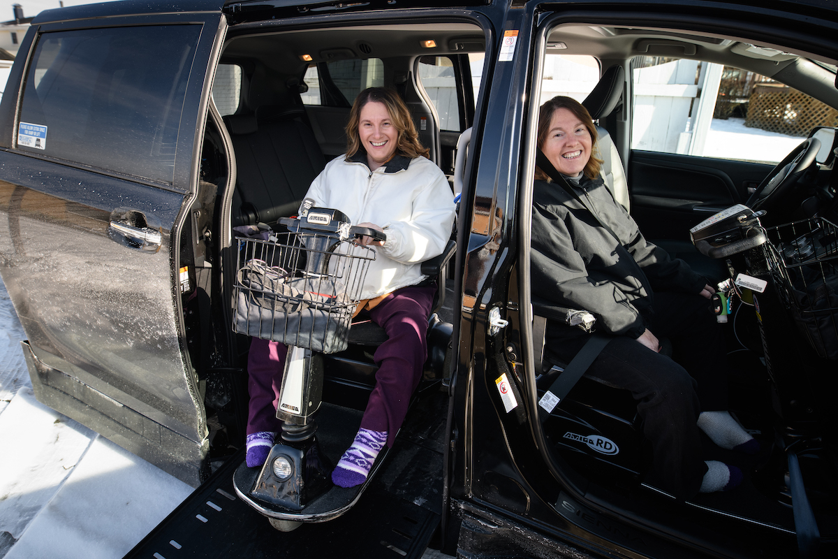 Two women seated in mobility scooters inside a modified van.