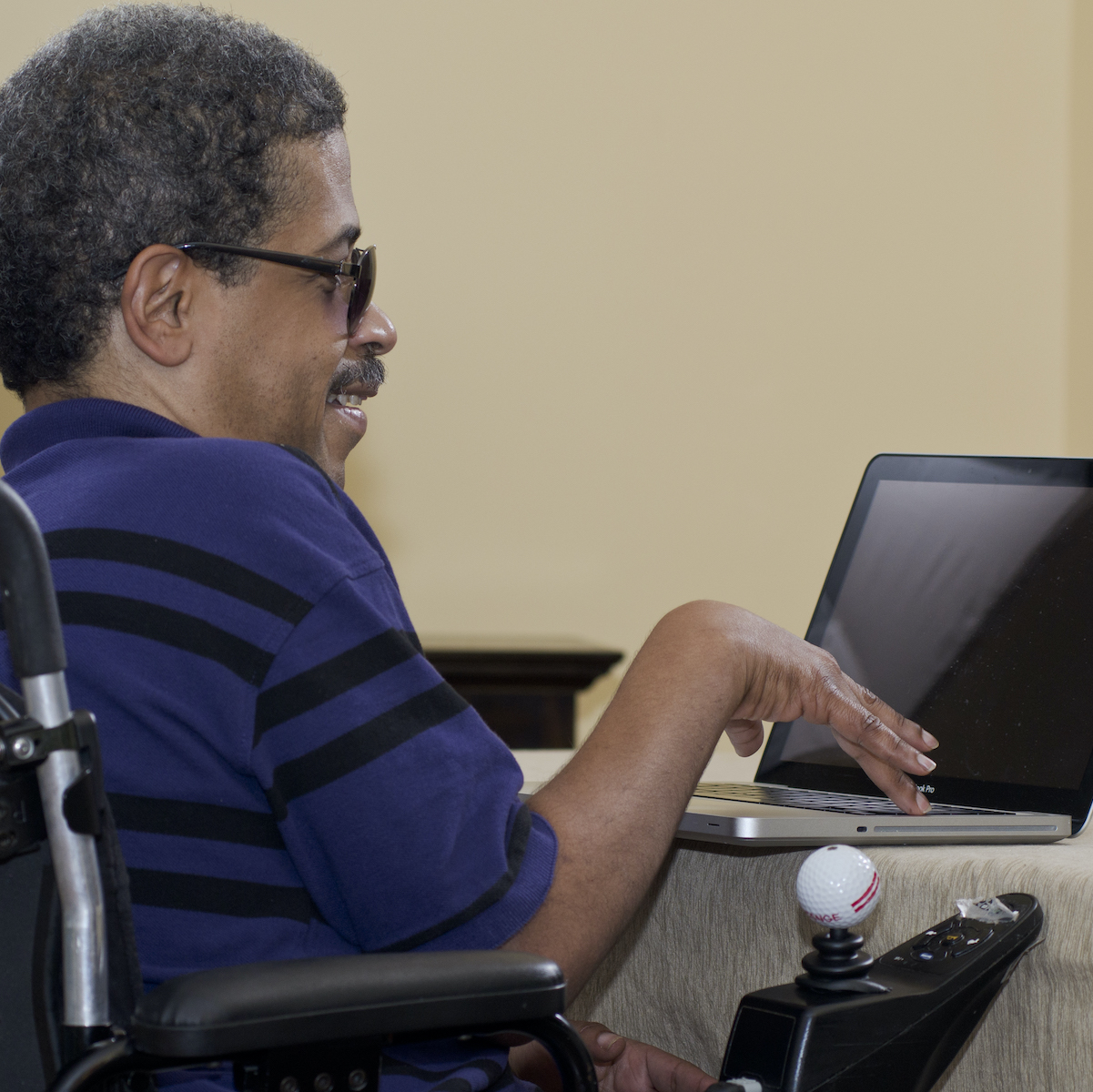 A man wearing sunglasses sits in a power wheelchair at a table while using a laptop computer.