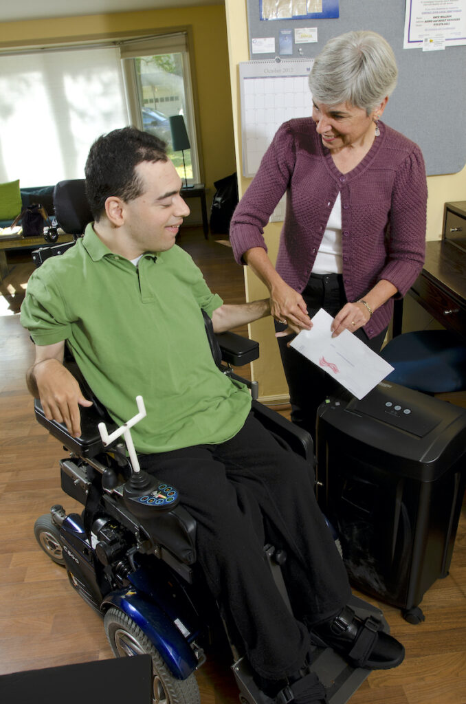 A man using a power wheelchair holds a piece of paper over a shredder with help from a woman standing next to him.
