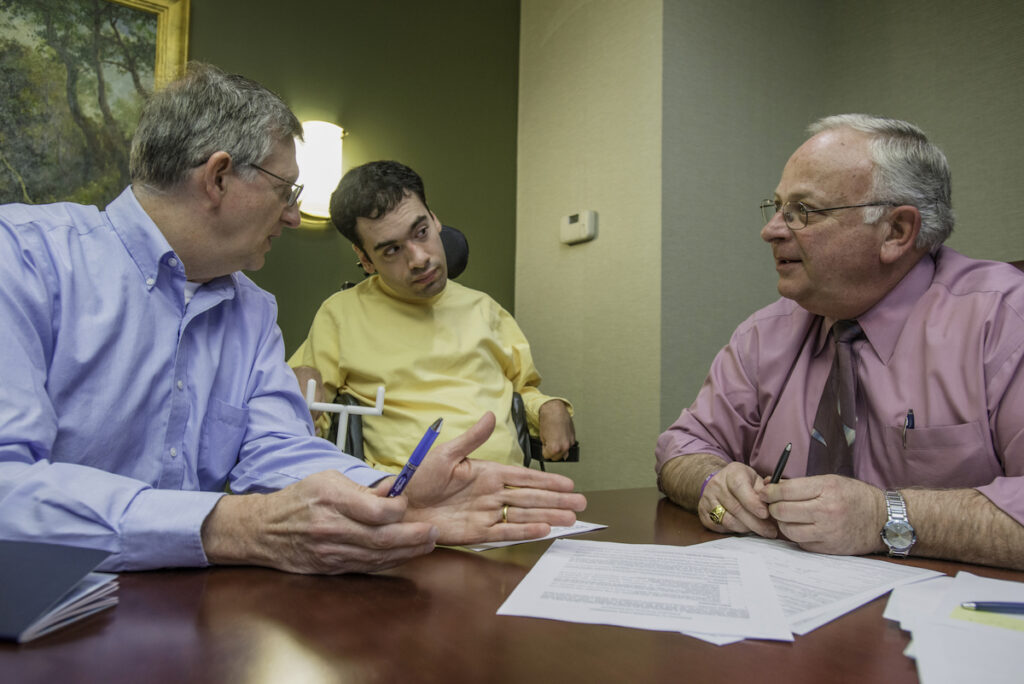 A young man using a power wheelchair sits with two older men around documents laid out on a table.