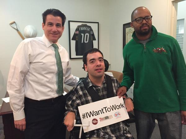 Three men pose together, one of whom uses a power wheelchair and holds a sign that reads #IWantToWork.