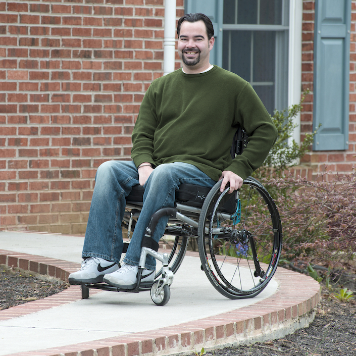 A man sits in his manual wheelchair on a concrete ramp walkway that leads to the front door of his home.