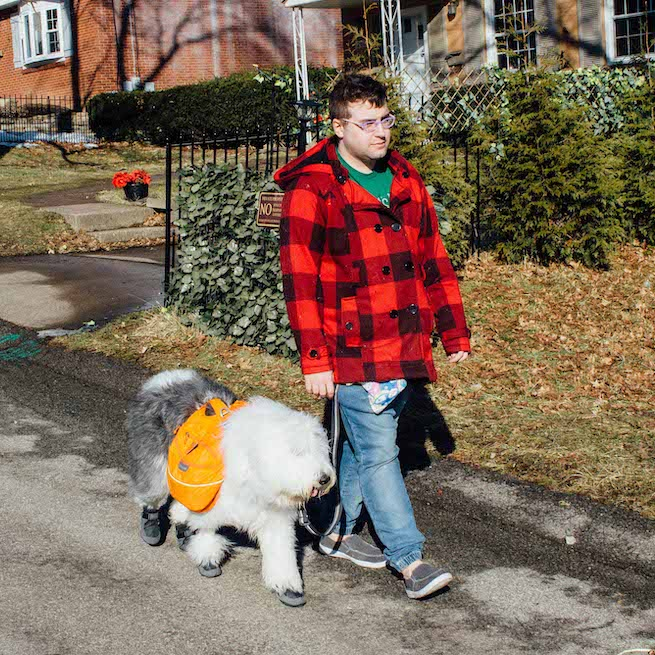 A man walks on a suburban street with his service dog.