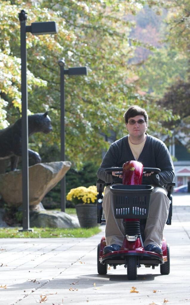 A young man rides a mobility scooter across a college campus.