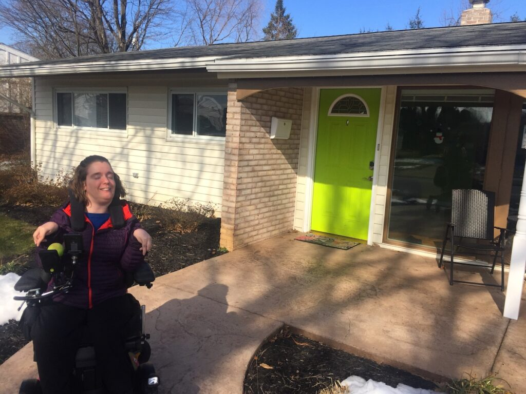 A woman using a power wheelchair smiles in front of her home with a concrete walkway ramp leading to a lime green front door.
