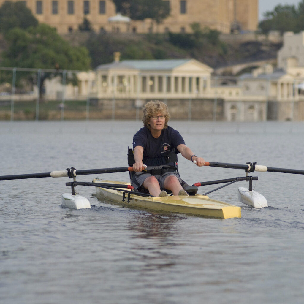 A woman rows a scull on a river with city architecture in the background.