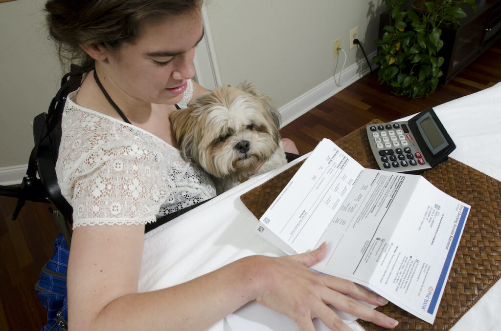A woman sits at a table looking at a bank statement with her dog in her lap.