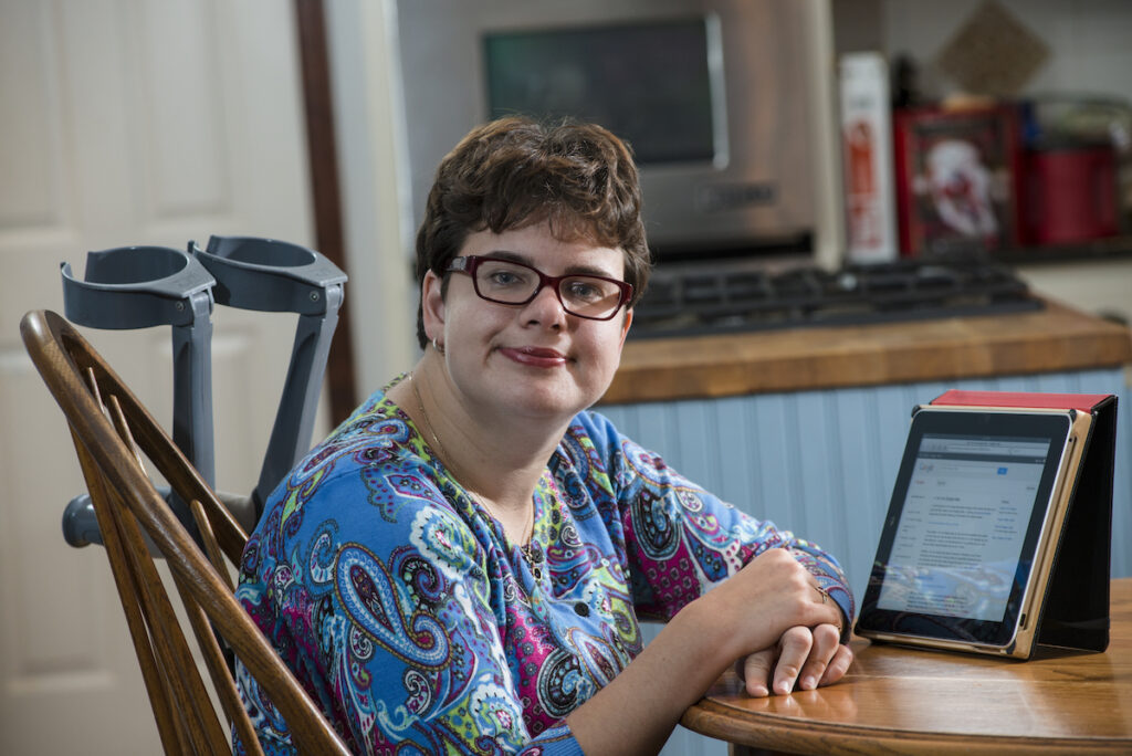 A young woman sits at a kitchen table with an iPad propped in front of her and crutches leaning on her chair.