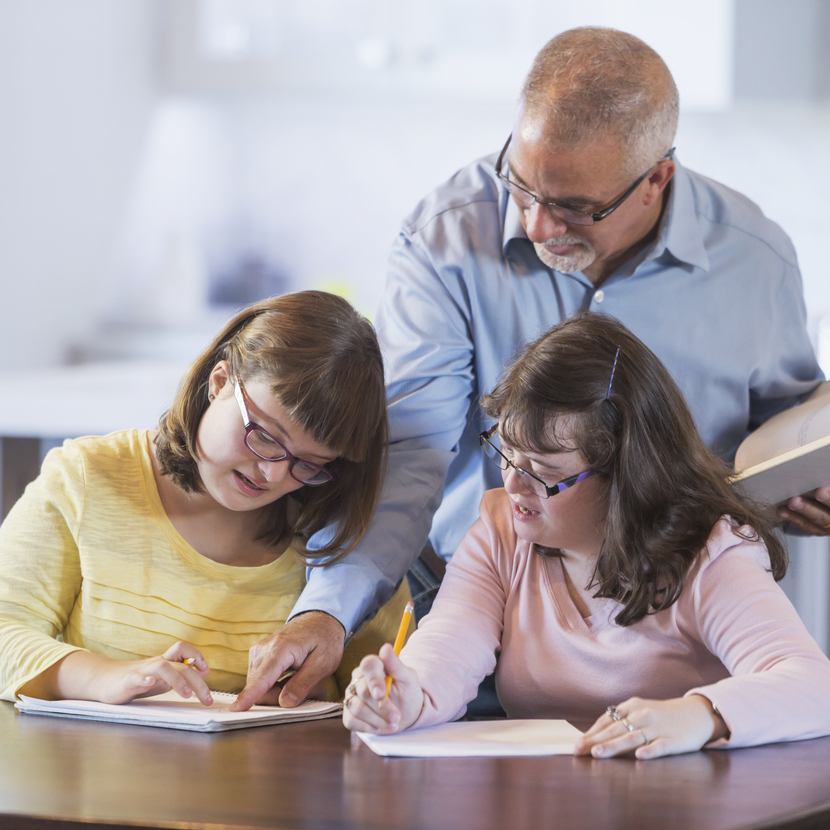 A father and two daughters with down syndrome doing homework. The girls are sitting at a table, writing with pencils. Father is standing behind them with an open book in his hand.