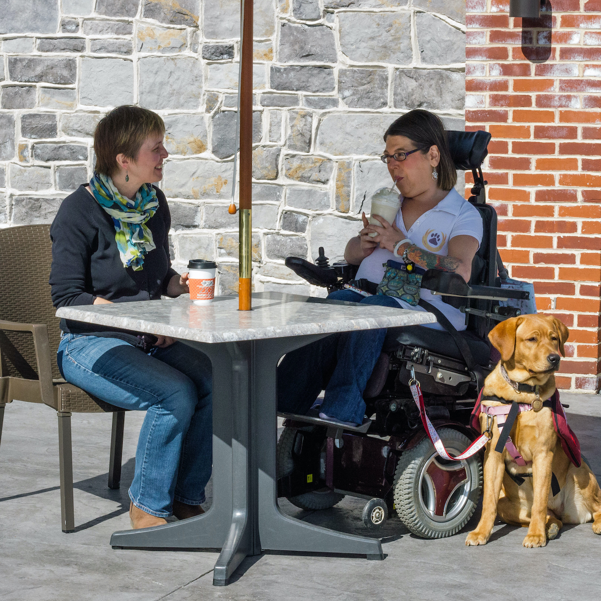 Two women sit outside at a cafe drinking coffee. One woman uses a power wheelchair and has her service dog next to her.