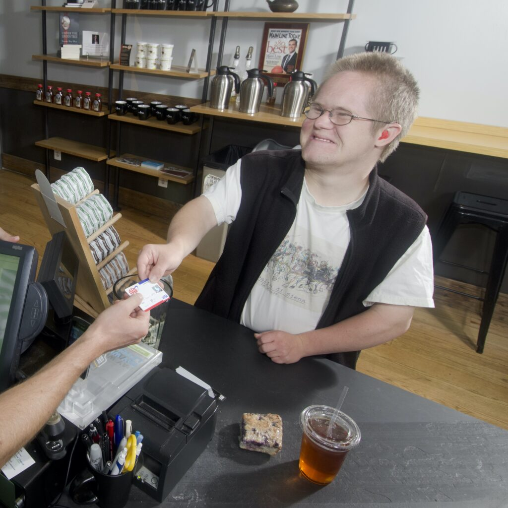 A smiling young man hands a debit card to a cashier. A bakery item and iced tea rest on the counter.