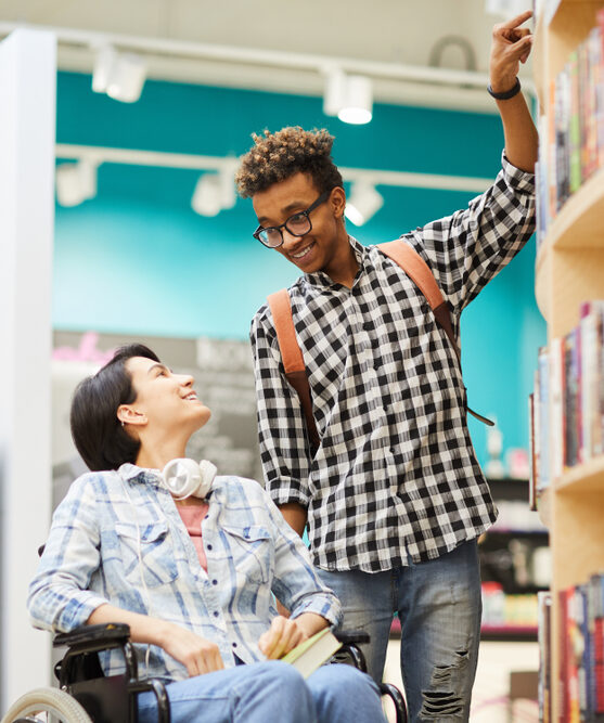 A young man smiles at a young woman who is using a manual wheelchair. He points to a book on a shelf in a bookstore.