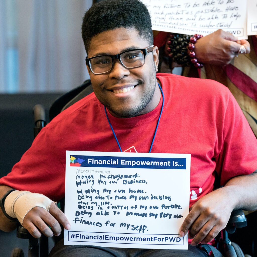 A young man holds a sign that says Financial Empowerment is... with a list of handwritten answers.