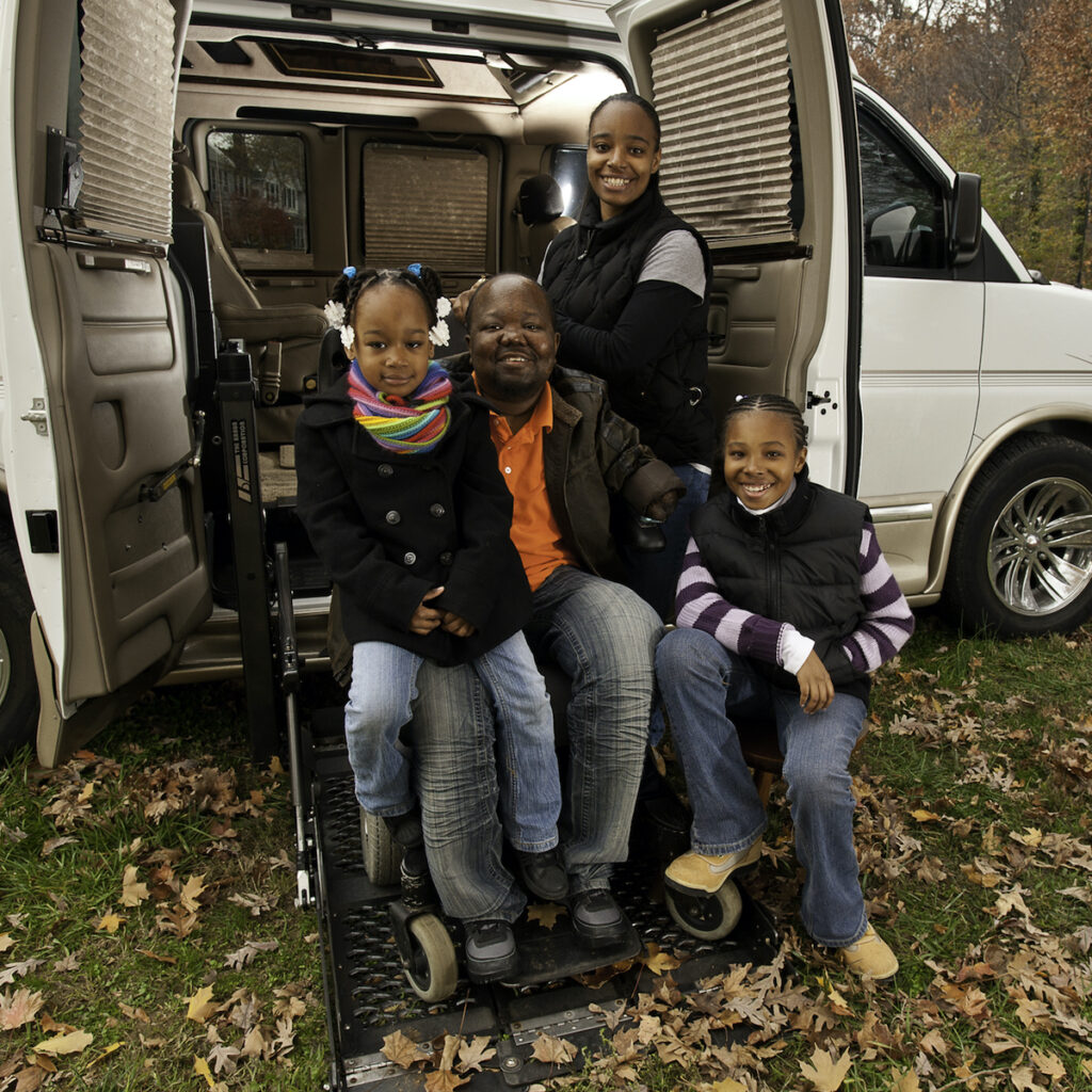 A man smiles with his family while sitting in a power wheelchair in front of an adapted van. His two daughters sit on his lap and his wife stands behind him.