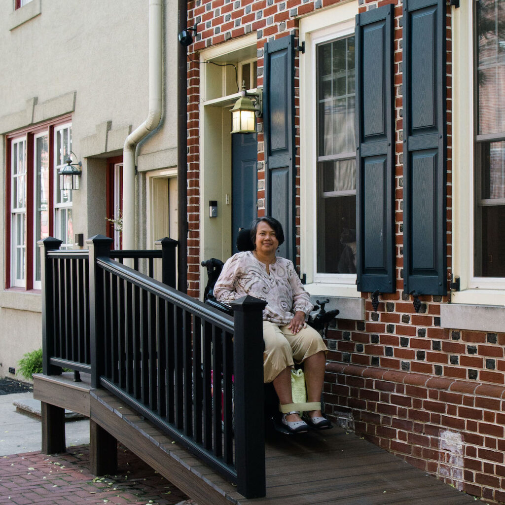 A woman smiles using her power wheelchair on a ramp in front of her townhouse.
