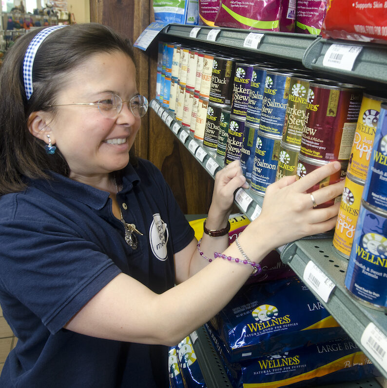 A young woman organizes shelves in a pet store.