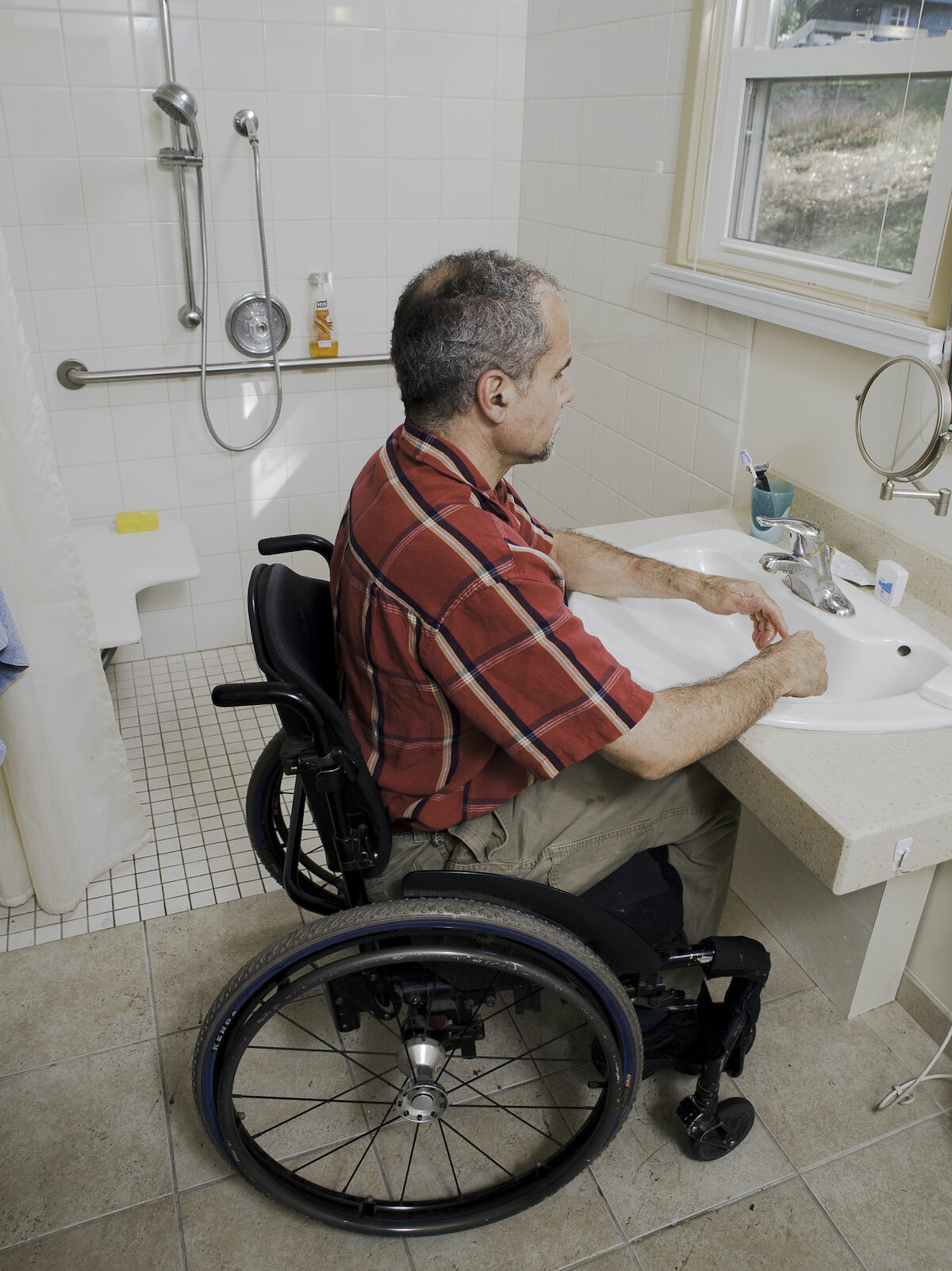 A man using a manual wheelchair washes his hands at an accessible sink next to a roll-in shower.
