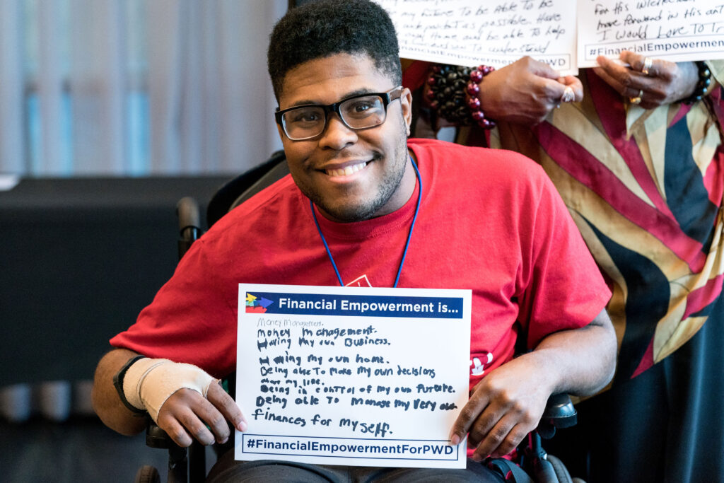 A young man holds up a sign that reads Financial Empowerment Is... with handwritten answers.