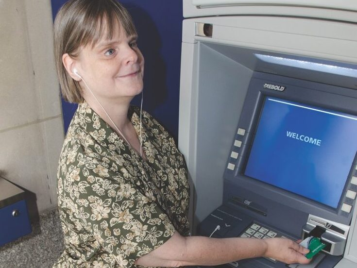 A woman stands with her guide dog at an ATM using headphones to hear the commands and pushing her debit card into the card reader.